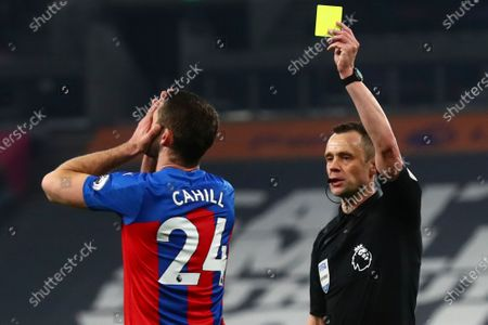 Crystal Palace's Gary Cahill is shown a yellow card during the English Premier League soccer match between Tottenham Hotspur and Crystal Palace at the Tottenham Hotspur Stadium in London