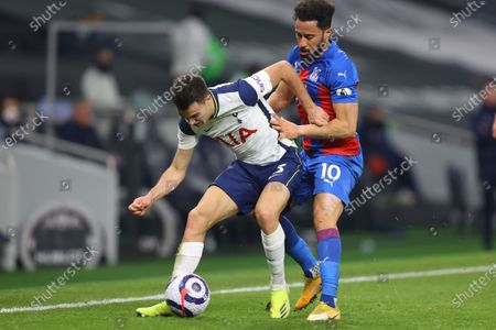 Tottenham's Sergio Reguilon, left, fights for the ball with Crystal Palace's Andros Townsend during the English Premier League soccer match between Tottenham Hotspur and Crystal Palace at the Tottenham Hotspur Stadium in London