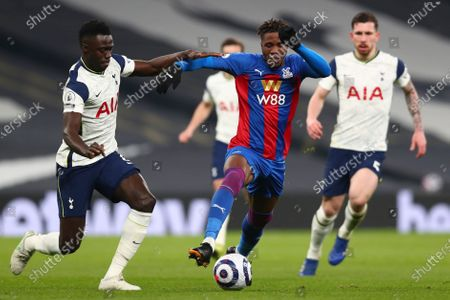 Crystal Palace's Wilfried Zaha, center, is challenged by Tottenham's Davinson Sanchez during the English Premier League soccer match between Tottenham Hotspur and Crystal Palace at the Tottenham Hotspur Stadium in London