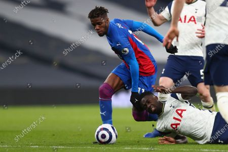 Crystal Palace's Wilfried Zaha, center, is challenged by Tottenham's Davinson, bottom, Sanchez during the English Premier League soccer match between Tottenham Hotspur and Crystal Palace at the Tottenham Hotspur Stadium in London