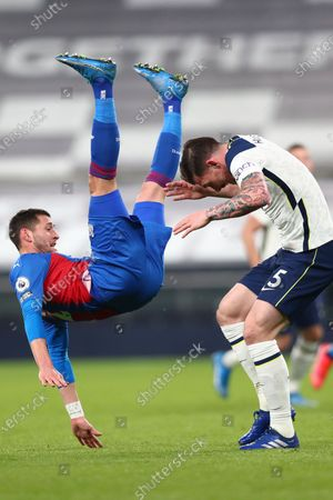 Crystal Palace's Gary Cahill, left, falls over Tottenham's Pierre-Emile Hojbjerg during the English Premier League soccer match between Tottenham Hotspur and Crystal Palace at the Tottenham Hotspur Stadium in London