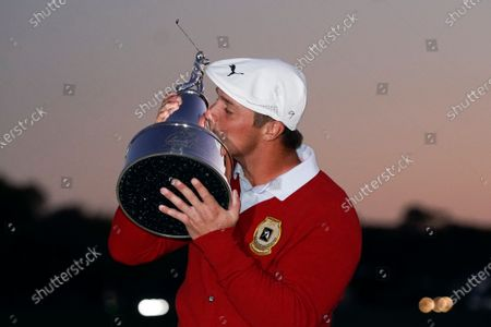 Bryson DeChambeau kisses the championship trophy after he won the Arnold Palmer Invitational golf tournament, in Orlando, Fla