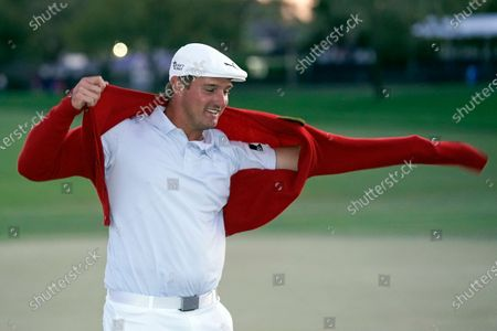 Bryson DeChambeau puts on the championship red sweater after winning the Arnold Palmer Invitational golf tournament, in Orlando, Fla