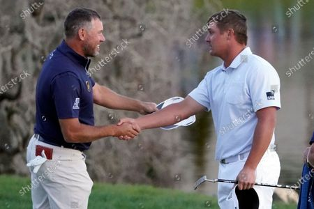 Lee Westwood, of England, and Bryson DeChambeau shake hands after they finished play in the Arnold Palmer Invitational golf tournament, in Orlando, Fla. DeChambeau won the tournament and Westwood finished second