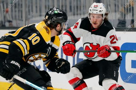 New Jersey Devils' Ty Smith (24) defends against Boston Bruins' Anders Bjork (10) during the second period of an NHL hockey game, in Boston