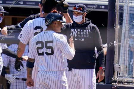 New York Yankees manager Aaron Boone, right, pats Gleyber Torres (25) on the helmet after he scored on a second inning grand slam by Brett Gardner during a spring training exhibition baseball game against the Philadelphia Phillies at George M. Steinbrenner Field in Tampa, Fla