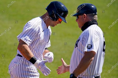 New York Yankees' Brett Gardner, left, rounds third to greetings from coach Phil Nevin after hitting a grand slam home run off Philadelphia Phillies starting pitcher Zack Wheeler during the second inning of a spring training exhibition baseball game at George M. Steinbrenner Field in Tampa, Fla