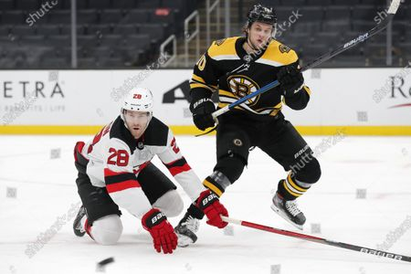 New Jersey Devils' Damon Severson (28) defends against Boston Bruins' Anders Bjork (10) during the second period of an NHL hockey game, in Boston