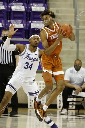 Texas forward Greg Brown, right, grabs a pass in front of TCU forward Kevin Easley (34) during the second half of an NCAA college basketball game in Fort Worth, Texas