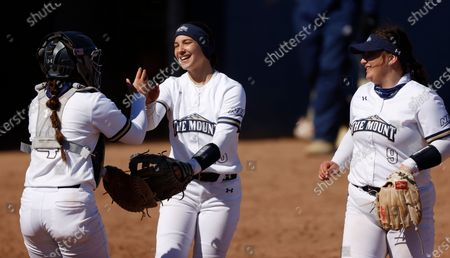 Mount St. Mary's Mountaineers from left: catcher Zoe Wilcox, third baseman Bridgette Gilliano and pitcher Elizabeth King celebrate getting an out and ending the inning against George Washington during an NCAA softball game, in Emmitsburg, Md