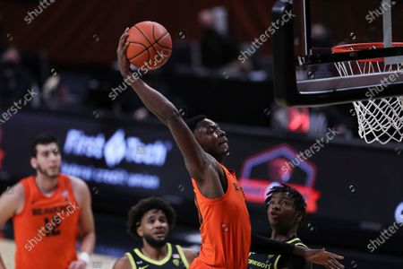 Oregon State's Warith Alatishe (10) dunks over Oregon's L.J. Figueroa, left, and Chandler Lawson, right, during the first half of an NCAA college basketball game in Corvallis, Ore
