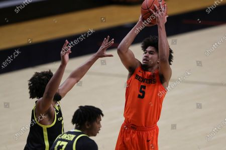 Oregon State's Ethan Thompson (5) shoots over Oregon's L.J. Figueroa, left, and Chandler Lawson, right, during the first half of an NCAA college basketball game in Corvallis, Ore