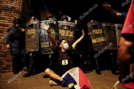 People defend police officers during a protest in front of the house of former President Horacio Cartes, in Asuncion, Paraguay, 07 March 2021. Hundreds of protesters gathered near the presidential palace to call for the resignation of President Mario Abdo Benitez ciriticizing his his management of the COVID-19 pandemic and the collapse of the health system.