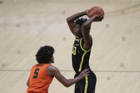Oregon's Eric Williams Jr. (50) looks for an open teammate to pass to away from Oregon State's Ethan Thompson (5) during the first half of an NCAA college basketball game in Corvallis, Ore
