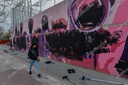 Stock Photo of Woman walks past a feminist mural vandalized during international women's day in Madrid, Spain, . The original mural celebrated pioneering women such as Rosa Parks, Frida Khalo, Angela Davis, or Valentina Tereshkova among others
