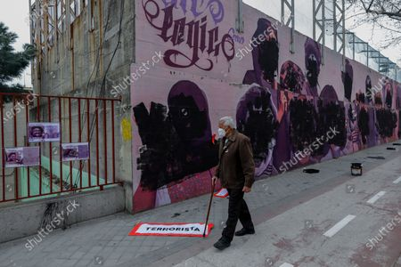 Stock Image of Man walks past a feminist mural vandalized during international women's day in Madrid, Spain, . The original mural celebrated pioneering women such as Rosa Parks, Frida Khalo, Angela Davis, or Valentina Tereshkova among others