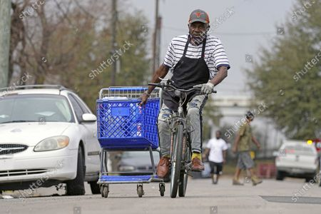 Stock Photo of Mark Johnson pulls a shopping cart with cases of donated water back to his home, which was without running water after a recent winter storm, in Houston. Local officials, including Houston Mayor Sylvester Turner, say they have focused their efforts during the different disasters on helping the underserved and under-resourced but that their work is far from complete