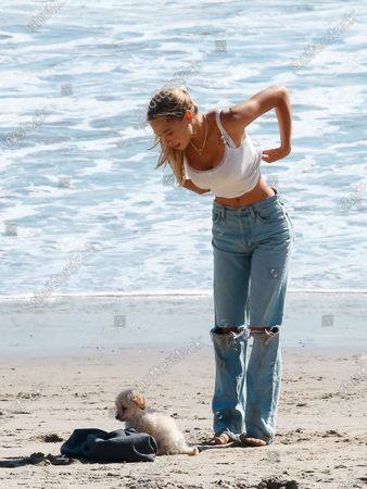 Alexis Ren playing with puppy Angel on the beach in Malibu