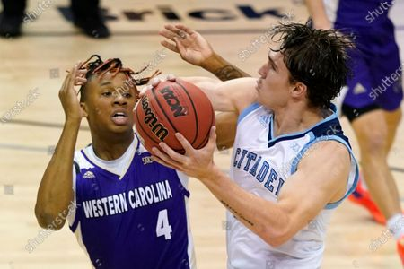 Stock Picture of Citadel forward Hayden Brown (33) drives the ball to the basket around Citadel guard Robert Guyton (4) in the first half of a first round NCAA men's college basketball championship game for the Southern Conference tournament, in Asheville, N.C