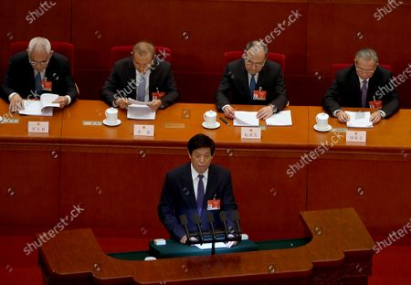 """Standing Committee Chairman Li Zhanshu delivers part of his annual work report to the Fourth Session of the 13th National People's Congress (NPC) held in the Great Hall of the People in Beijing on Monday, March 8, 2021. China will speed up lawmaking aimed at countering foreign sanctions and """"long-arm jurisdiction"""" primarily aimed at the U.S.'s use of sanctions on China for its policies, according to its annual work report at the parliamentary session."""