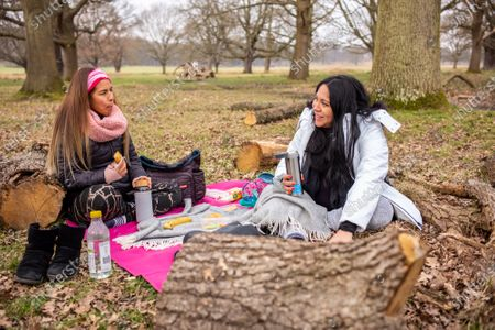 Stock Photo of Friends Nati Siu 38 (left) and Sandra Chavez 42 meet for the first time since October 2020 as they enjoy a picnic in Richmond Park, South West London this afternoon. From today, two friends are now allowed to socialise out side of their household for a coffee or picnic for the first time in months. England begins Stage1 of the easing of lockdown today, with children returning to school, care homes allowing a visitor and friends being allowed to socialise out side of their bubble. However, pubs, shops and restaurants still remain closed.