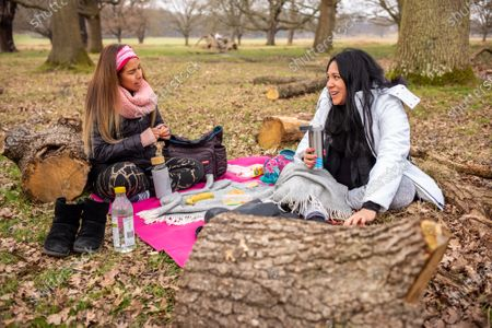 Friends Nati Siu 38 (left) and Sandra Chavez 42 meet for the first time since October 2020 as they enjoy a picnic in Richmond Park, South West London this afternoon. From today, two friends are now allowed to socialise out side of their household for a coffee or picnic for the first time in months. England begins Stage1 of the easing of lockdown today, with children returning to school, care homes allowing a visitor and friends being allowed to socialise out side of their bubble. However, pubs, shops and restaurants still remain closed.