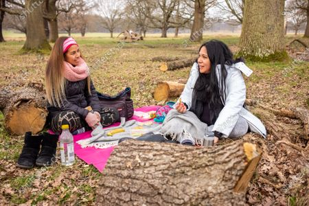 Stock Image of Friends Nati Siu 38 (left) and Sandra Chavez 42 meet for the first time since October 2020 as they enjoy a picnic in Richmond Park, South West London this afternoon. From today, two friends are now allowed to socialise out side of their household for a coffee or picnic for the first time in months. England begins Stage1 of the easing of lockdown today, with children returning to school, care homes allowing a visitor and friends being allowed to socialise out side of their bubble. However, pubs, shops and restaurants still remain closed.