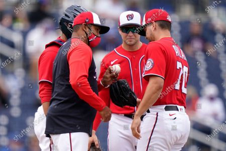 Washington Nationals manager Dave Martinez, left, hands the ball to relief pitcher Luis Avilan (70) during the second inning of a spring training baseball game against the New York Mets, in West Palm Beach, Fla