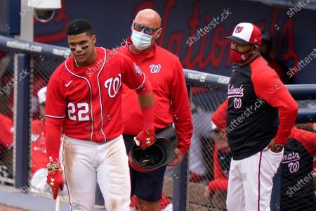 Washington Nationals' Juan Soto (22) talks with manager Dave Martinez, right, and a member of the coaching staff after a close pitch thrown by New York Mets starting pitcher Jordan Yamamoto during the third inning of a spring training baseball game, in West Palm Beach, Fla