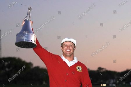 Bryson DeChambeau holds up his championship trophy after winning the Arnold Palmer Invitational golf tournament, in Orlando, Fla
