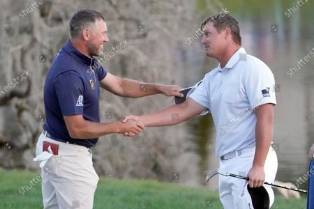 Lee Westwood, left, of England, and Bryson DeChambeau shake hands after they finished play in the Arnold Palmer Invitational golf tournament, in Orlando, Fla. DeChambeau won the tournament and Westwood finished second
