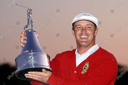 Stock Picture of Bryson DeChambeau holds up his championship trophy after winning the Arnold Palmer Invitational golf tournament, in Orlando, Fla