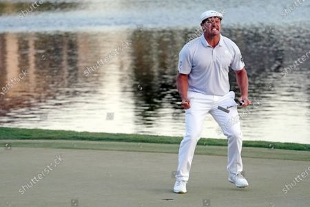 Stock Photo of Bryson DeChambeau celebrates after sinking his final putt to win the Arnold Palmer Invitational golf tournament, in Orlando, Fla
