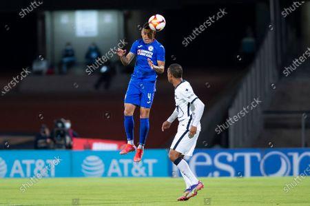 Julio Cesar Dominguez #4 of Cruz Azul fights for the ball against Gabriel Torres #8 of Pumas UNAM