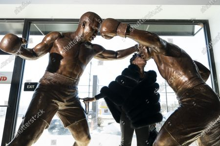 Weatta Frazier Collins kisses a statue of her father Joe Frazier, right, fighting Muhammad Ali, on the 50th anniversary of the boxers' World Heavyweight championship boxing bout, at the Joe Hand Gym in Feasterville, Pa