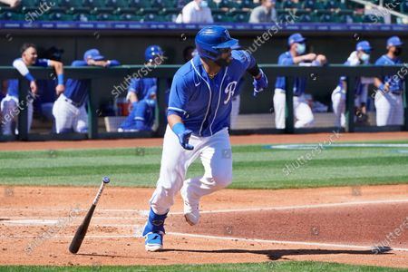 Kansas City Royals' Carlos Santana drops his bat on his way to first base with an RBI-single in the first inning of a spring training baseball game against the Oakland Athletics, in Surprise, Ariz