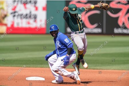 Oakland Athletics second baseman Tony Kemp, right, moves out of the way of Kansas City Royals' Carlos Santana after forcing out Santana at second base and completing the throw to first on a double-play ball hit by Salvador Perez in the first inning of a spring training baseball game, in Surprise, Ariz