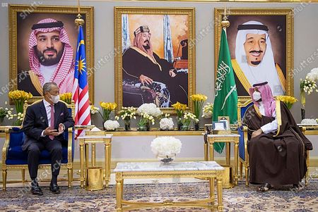 In this photo released by Saudi Press Agency, SPA, Saudi Crown Prince Mohammed bin Salman, right, meets with Malaysian Prime Minister Muhyiddin Yassin, in Riyadh, Saudi Arabia, late . Portraits in the background show Saudi King Salman, right, his Crown Prince Mohammed bin Salman, left, and Saudi Arabia's founder late King Abdul Aziz Al Saud