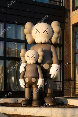 """A large-scale sculpture titled """"WAITING"""" by artist KAWS outside """"The Greenpoint"""" development along the Brooklyn waterfront"""