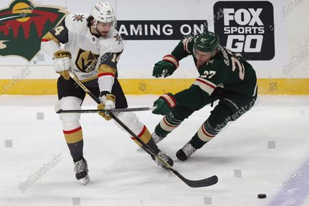 Vegas Golden Knights' Nicolas Hague (14) handles the puck against Minnesota Wild's Nick Bjugstad (27) in the first period of an NHL hockey game, in St. Paul, Minn