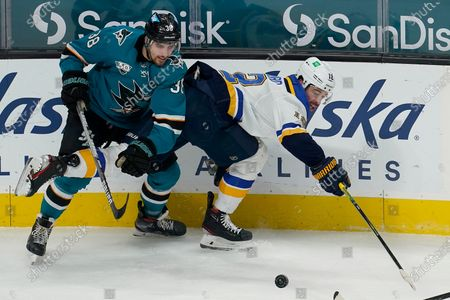 St. Louis Blues left wing Zach Michael Sanford, right, reaches for the puck next to San Jose Sharks defenseman Mario Ferraro (38) during the third period of an NHL hockey game in San Jose, Calif