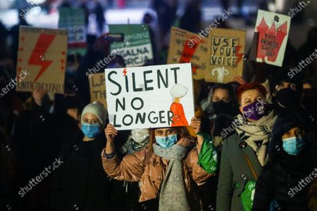 Stock Picture of People demonstrate against restrictions on abortion law on Women's Day. Krakow, Poland on March 8, 2021. The protest was organized by Women Strike to protest against the law that states that all abortions in Poland are banned except in cases of rape and incest and when the mother's life or health are considered to be at risk.