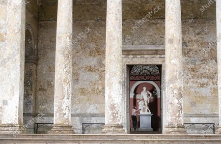 Stock Image of Collections and House officer, Lucy Cooper uses specialist equipment to clean the Pantheon. She is pictured cleaning the Herculeus statue inside the temple.   Herculean effort  A major spring clean is taking place at one of Britain's most famous temples as it prepares for the time when it can reopen. The Pantheon at Stourhead was designed by the architect Henry Flitcroft and built between 1753 and 1754.    It is loosely modelled on the Pantheon in Rome and was originally called the Temple of Hercules.  The limestone temple was commissioned by Henry Hoare II, known as 'Henry the Magnificent', an English banker and garden designer.  It contains statues of Hercules, Diana, Flora, Isis and St Susanna and Horace Walpole said in 1762 it had few rivals 'in magnificence, taste and beauty'.