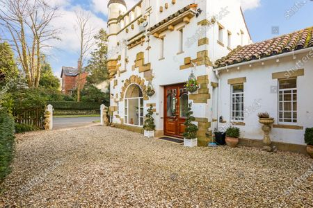 Stock Photo of A quirky 116-year-old mini castle that has a tower roof terrace with far-reaching views is on the market for £925,000.  Grade II Listed High Morland Lodge is a five-storey Italianate property that has been sympathetically restored by its current owner.  The elaborate home in Knutsford, Cheshire, was originally built in 1905 as a gatehouse and designed by Richard Harding-Watt, who was a well-know designer in the area and lived in the same road as this property until 1913.  Most of the living space is spread over the three lower floors, with a roof terrace at the fourth storey and an office at the top to make the most of the impressive views.