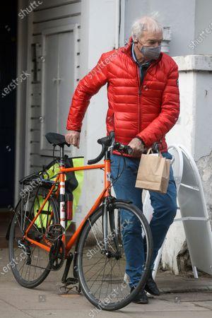 Exclusive - Journalist Jon Snow is seen pushing his bike in London