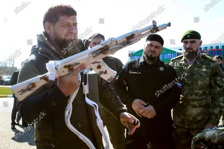 Chechnya's regional leader Ramzan Kadyrov holds a white painted Kalashnikov machine gun as he inspects troops before their deployment for an exercise in the Arctic at an airport outside Grozny, Russia