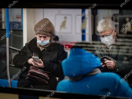 An elderly woman wearing a protective face mask sits in Moscow's Metro during the pandemic of SARS-CoV-2 coronavirus in Moscow, Russia, 09 March 2021. Moscow's Mayor Sergei Sobyanin has canceled mandatory self-isolation for people over 65 and those with chronic diseases in Moscow. According to the official information, in the past 24 hours Russia registered 9445 included 1066 in Moscow new cases caused by the SARS-CoV-2 coronavirus infection.