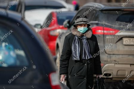 An elderly woman wearing a protective face mask walks during the pandemic of SARS-CoV-2 coronavirus in Moscow, Russia, 09 March 2021. Moscow's Mayor Sergei Sobyanin has canceled mandatory self-isolation for people over 65 and those with chronic diseases in Moscow. According to the official information, in the past 24 hours Russia registered 9445 included 1066 in Moscow new cases caused by the SARS-CoV-2 coronavirus infection.