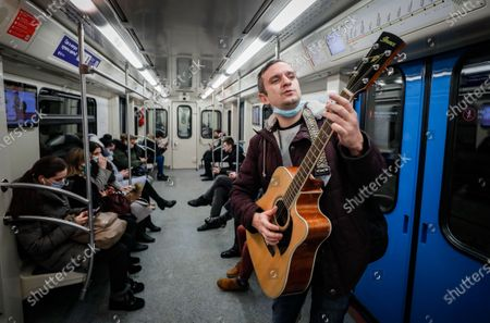 A musician plays his guitar in Moscow's Metro during the pandemic of SARS-CoV-2 coronavirus in Moscow, Russia, 09 March 2021. Moscow's Mayor Sergei Sobyanin has canceled mandatory self-isolation for people over 65 and those with chronic diseases in Moscow. According to the official information, in the past 24 hours Russia registered 9445 included 1066 in Moscow new cases caused by the SARS-CoV-2 coronavirus infection.