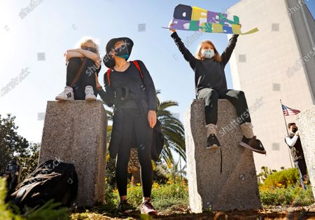 Viviana Harran, center, and her children Westley, 7, left, and Sandra, 9, right, of South Los Angeles, participate in a demonstration outside the West L.A. Federal Building where participating parents from 20 schools stage a Zoom blackout, wearing black clothing and withholding their children from online classes, to pressure the L.A. Unified School District to bring students back for in-person instruction and other services on Monday, February 22, 2021. (Christina House / Los Angeles Times)